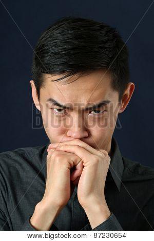 Angry young Asian man looking at camera
