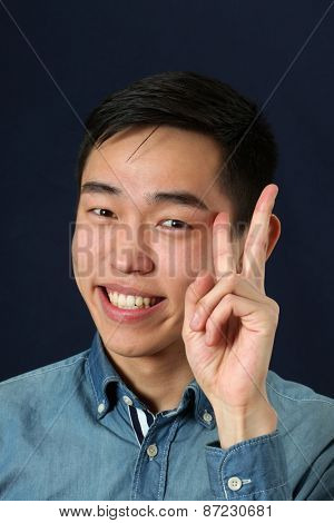 Smiling young Asian man giving victory sign and looking at camera