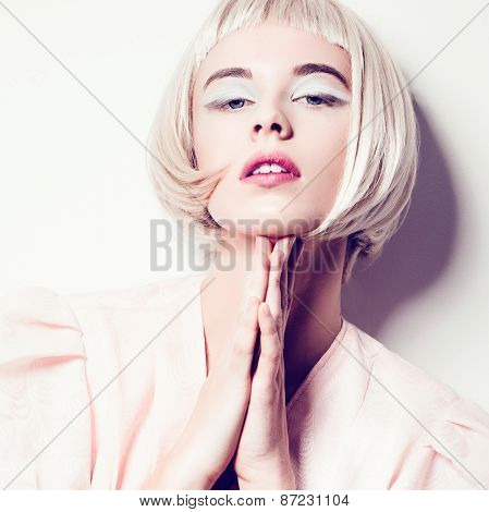 Portrait Of A Beautiful Young Blond Woman With Short Hair In Studio On A White Background