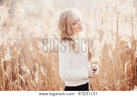 Portrait Of A Beautiful Young Blonde Girl In A Field In White Pullover, Smiling With Eyes Closed, Co