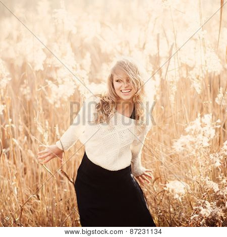 Portrait Of A Beautiful Young Blonde Girl In A Field In White Pullover, Smiling, Concept Of Beauty A