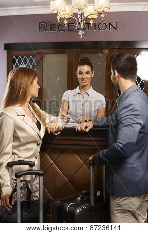 Happy female receptionist giving information to guests upon arrival.