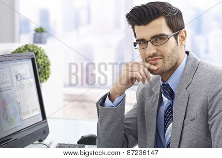 Portrait of handsome young businessman in bright office.