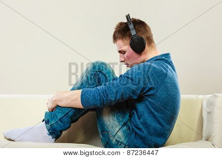 Young Man With Headphones On Couch