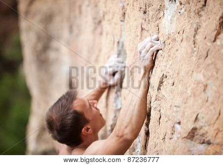 Cropped view of male rock climber on cliff