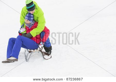 Young man embracing woman on sled in snow