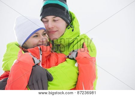 Loving young couple in warm clothing embracing outdoors