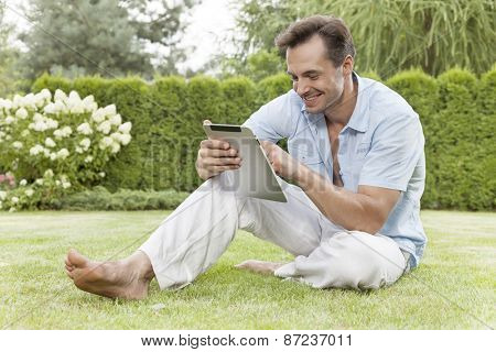 Full length of smiling young man using digital tablet in park