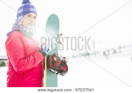 Beautiful young woman in warm clothing holding snowboard during winter
