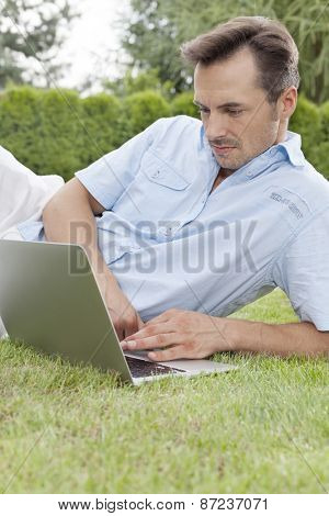 Young man using laptop in park