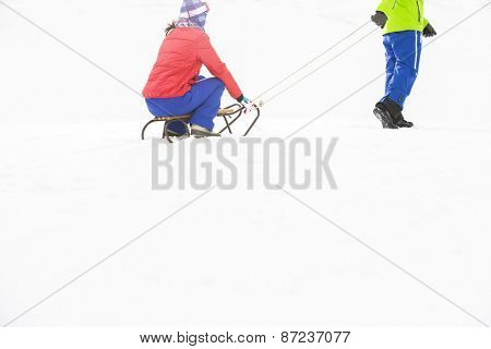 Low section of young man pulling woman on sled