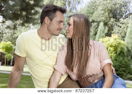 Romantic young couple looking at each other in park