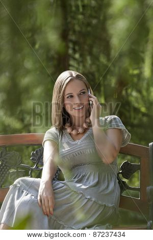 Beautiful young woman using mobile phone on park bench