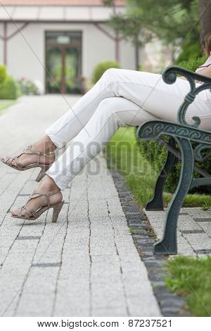 Low section of young woman with high heels sitting on park bench