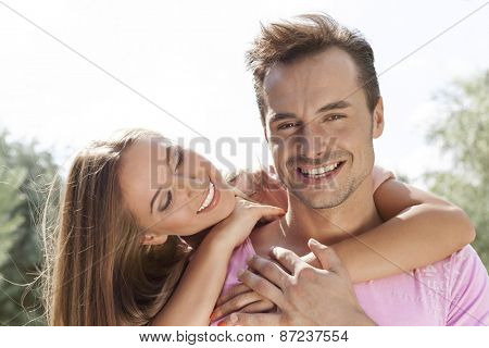 Smiling young woman embracing man from behind in park