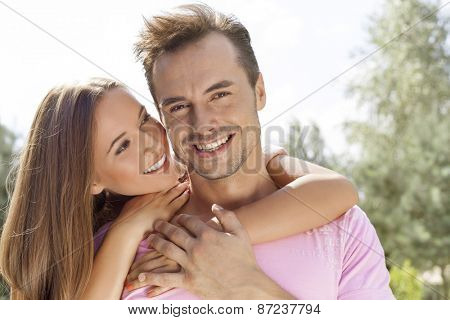 Beautiful young woman embracing man from behind in park