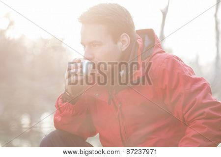 Male hiker drinking coffee in forest