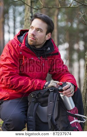 Young male hiker with backpack in forest