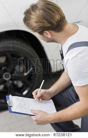 Side view of automobile mechanic writing on clipboard while examining car's wheel in workshop