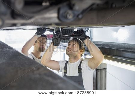 Maintenance engineers repairing car in workshop