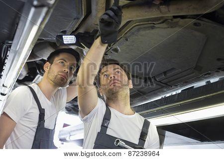 Male mechanics examining car in workshop