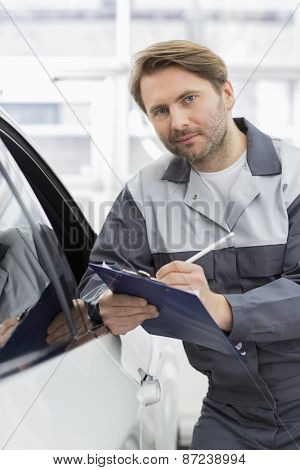 Portrait of confident mechanic holding clipboard while leaning on car's window in workshop