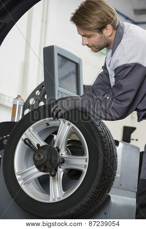 Cropped image of automobile mechanic repairing car's wheel in workshop