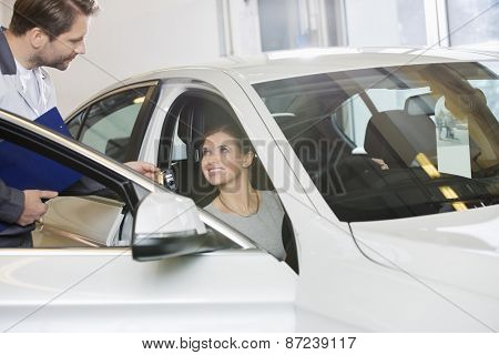 Female customer receiving car key from mechanic in automobile repair shop