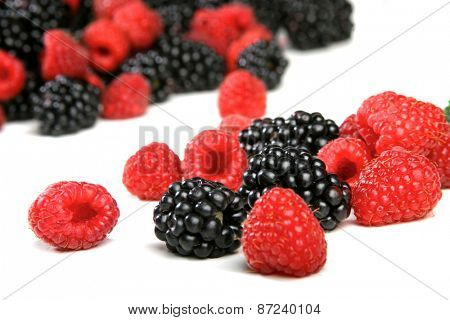 Raspberries and blackberries on white background