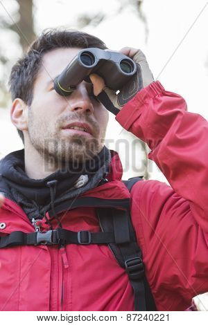 Young male backpacker using binoculars in forest