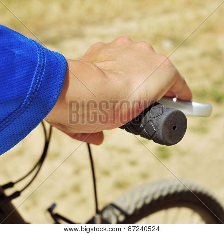 closeup of a young man riding a mountain bike on a dirt road