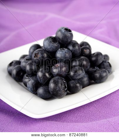 Blueberries on white plate - close up