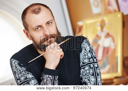 Religious icon painter male portrait in front of an orthodox icon with brush at workshop
