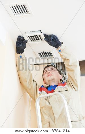 industrial worker installing ventilation or air conditioning filter holder in ceiling