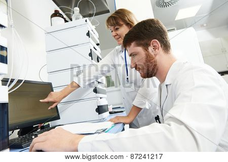 researchers team work on computer with scientific analysing data out scientific test in chemistry laboratory