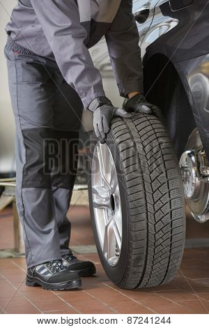 Low section of repairman fixing car's tire in workshop