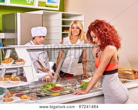 Women at cafeteria buying food. Seller man.