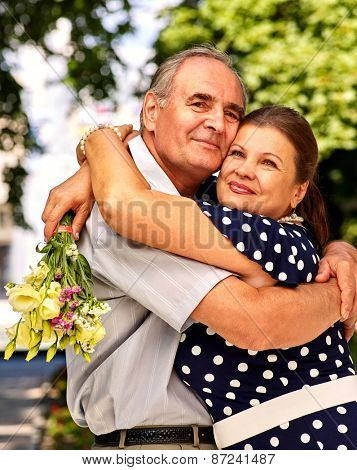 Happy old couple at summer  outdoor. Elderly people hugging