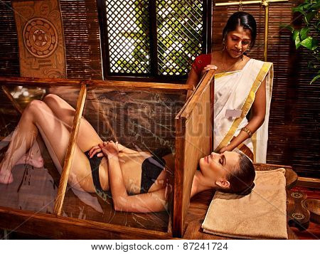 Woman having Ayurvedic India sauna treatment.