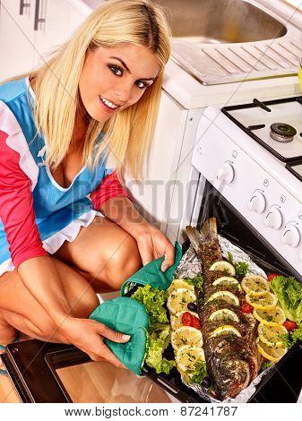 Happy woman prepare fish in oven.