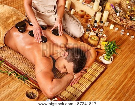 Man getting stone therapy massage in bamboo spa. Lying on floor.