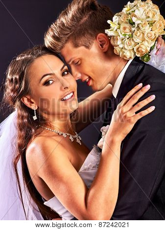 Bride and groom wearing wedding dress and costume. Black background.