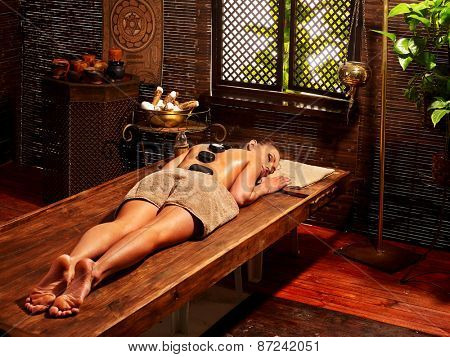 Young woman having Ayurveda stone massage. One people.