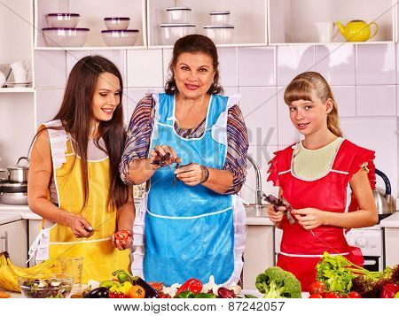 Family with grandmother and child at kitchen. Grandma teaches cooking.