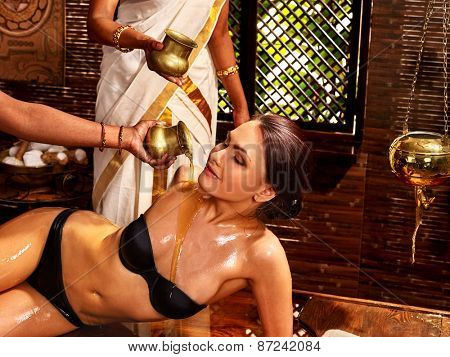 Young woman having ayurveda spa treatment. Pouring oil.