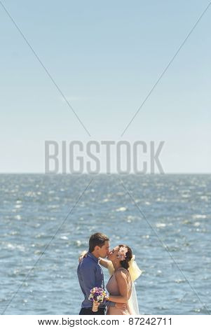 beautiful young newlywed couple on wooden bridge near sea embracing and kissing