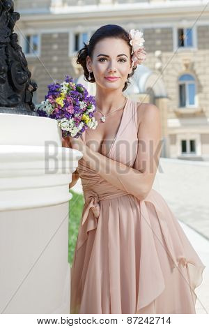 beautiful happy bride in beige dress with plunging neckline smiling standing near city building