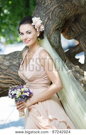 beautiful happy bride in beige dress with plunging neckline smiling standing among green trees