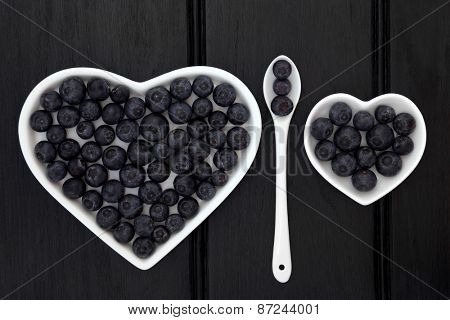 Blueberry fruit in heart shaped dishes and porcelain spoon over dark wood background.