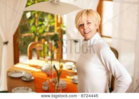 Woman setting the table for tea of coffee time